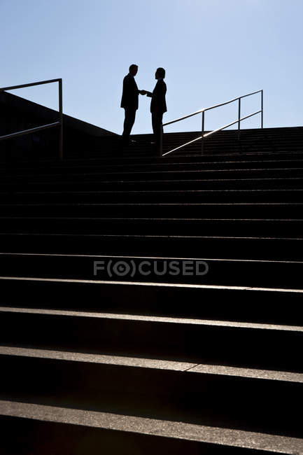 Two silhouetted businessmen shaking hands at stairs — Stock Photo