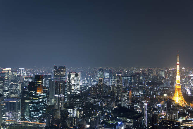Cityscape of illuminated Tokyo Tower amidst skyscrapers at night — Stock Photo