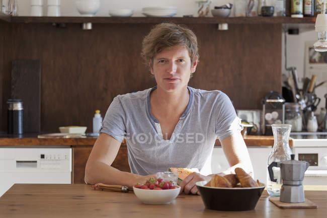 Retrato de jovem homem sentado na mesa de jantar com café da manhã — Fotografia de Stock