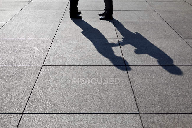 Shadow of two businessmen shaking hands — Stock Photo