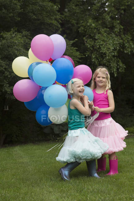 Happy siblings holding balloons in backyard — Stock Photo