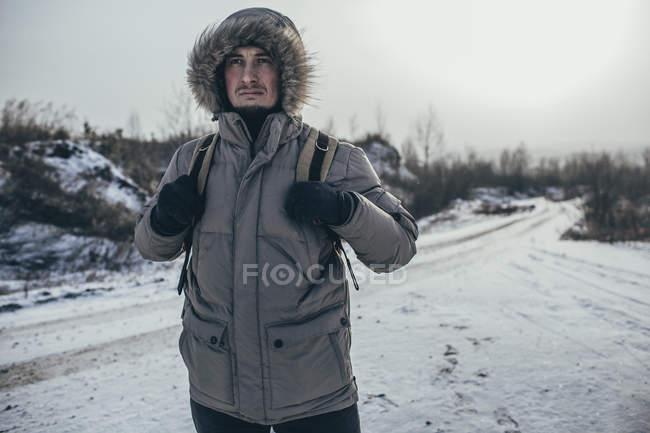 Nachdenklicher Wanderer mit Rucksack stehend auf verschneite Landschaft — Stockfoto