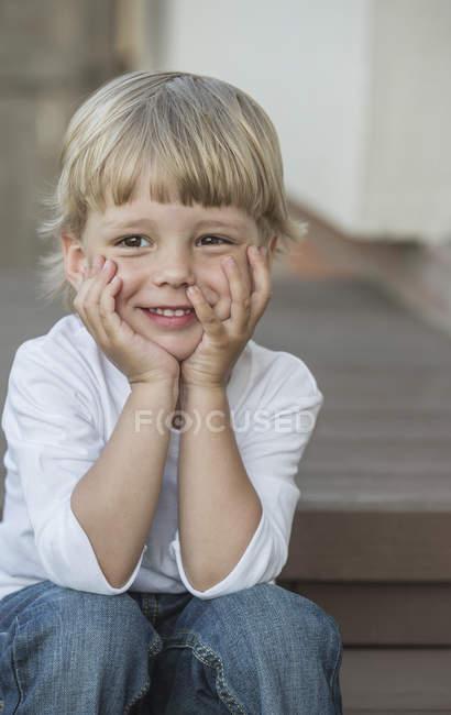 Симпатичный мальчик сидит с головой на крыльце — стоковое фото