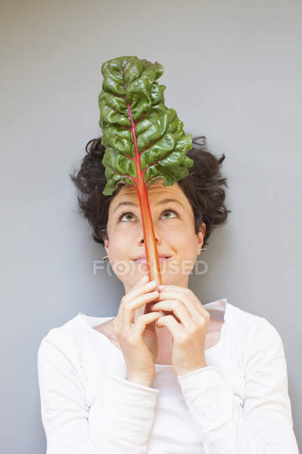 Smiling woman holding rhubarb leaf on nose and looking up over grey background — Stock Photo