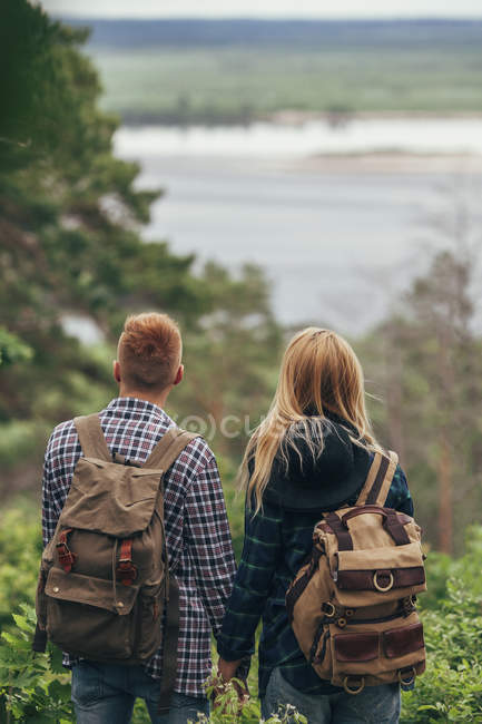 Couple wearing backpacks standing in forest — Stock Photo