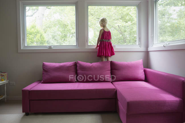 Girl standing on pink sofa by window at home — Fotografia de Stock