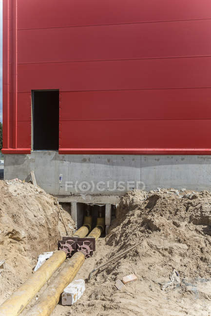 Pipe lines running under building at construction site — Stock Photo