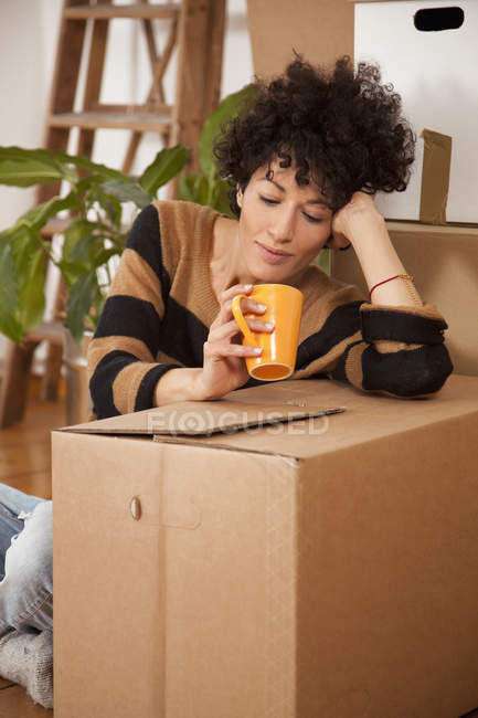 Tired woman taking coffee break while moving house — Stock Photo