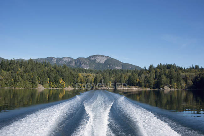 Ferry wakes in lake with mountains on background — Stock Photo
