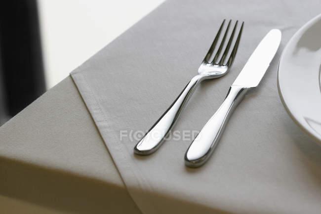 Nahaufnahme von Messer und Gabel auf Tischdecke — Stockfoto