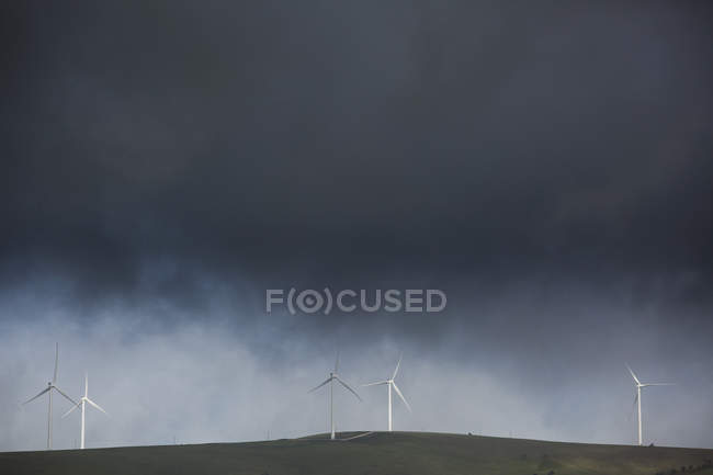 Wind turbines on agricultural field over tough cloudscape — Stock Photo