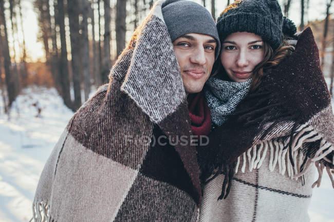 Портрет улыбающейся пары, завернутой в одеяло, стоя на заснеженном поле — стоковое фото