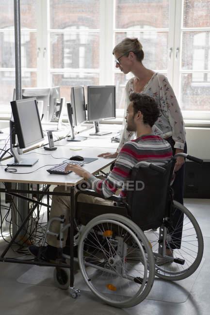 Мужчина и женщина работают за компьютером в офисе — стоковое фото