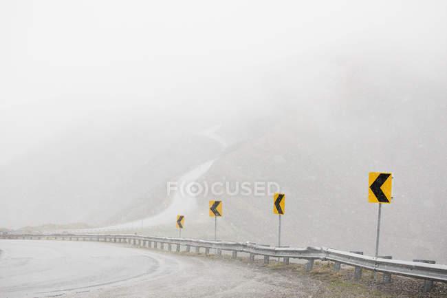 Rangée de panneaux routiers sur la route de montagne par temps brumeux — Photo de stock