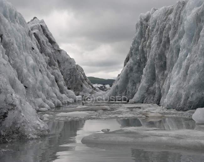 Canal au milieu du glacier contre un paysage nuageux difficile — Photo de stock