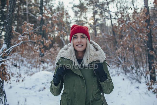Giovane donna che indossa cappello e giacca in maglia mentre distoglie lo sguardo — Foto stock