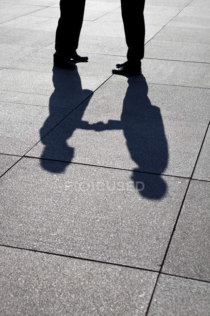 Silhouettes of two businessmen shaking hands — Stock Photo