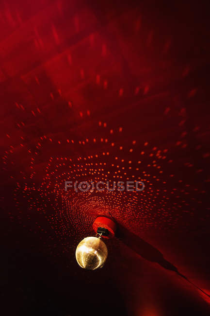 Disco ball on red lit ceiling in nightclub — стоковое фото