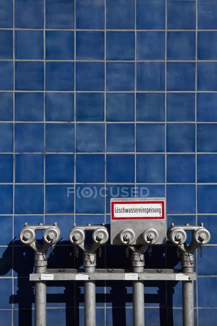 Tuyaux d'incendie contre le mur carrelé bleu — Photo de stock