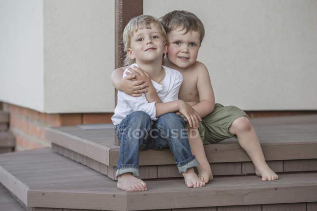 Retrato completo de los niños sentados brazo alrededor en el porche - foto de stock