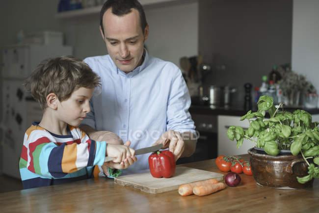 Filho de ensino do pai para cortar vegetais na cozinha — Fotografia de Stock