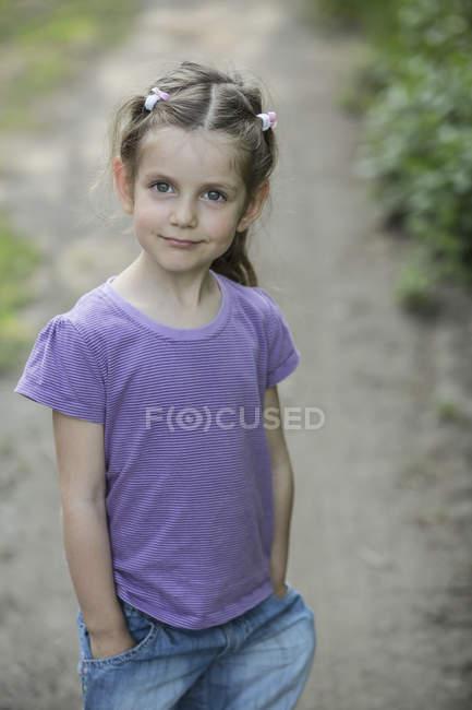 Uma jovem sorridente, de pé em uma estrada de terra — Fotografia de Stock