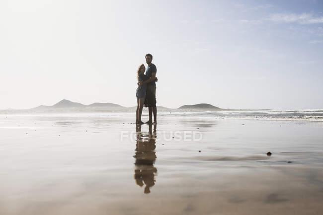 Amorosa pareja abrazándose en la playa en día soleado - foto de stock