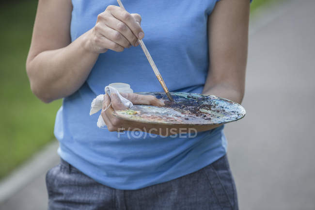 Midsection of female painter mixing paints on palette in park alley — Stock Photo