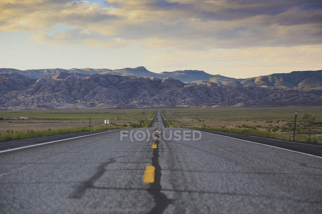 Road leading towards rocky mountains against cloudy sky — Stock Photo