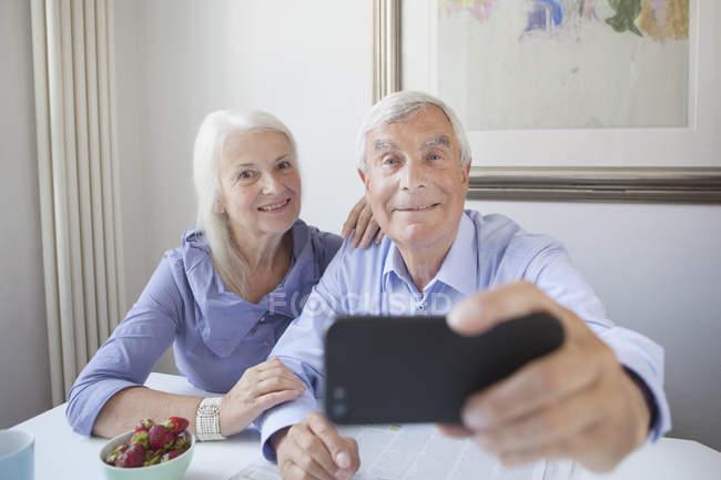 Felice coppia anziana prendendo autoritratto con smartphone a tavola — Foto stock