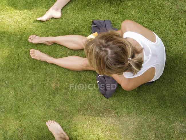 Зверху зору жінка, сидячи на траві — стокове фото