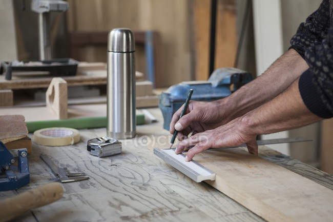 Cropped image of male carpenter marking on wood in workshop — Stock Photo