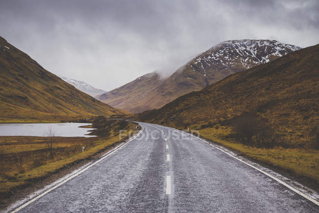 Road passing by mountains against cloudy sky — Stock Photo