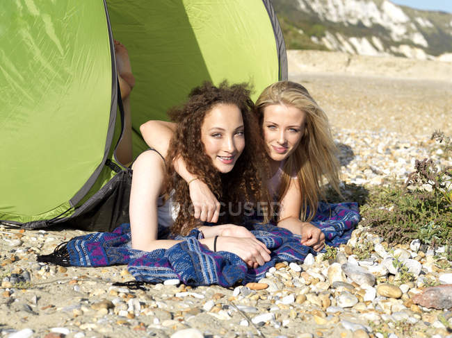 Two friends lying partially inside a beach tent on a rocky beach — Stock Photo