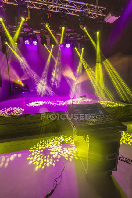 Sound mixer in front of illuminated stage in studio — Stock Photo