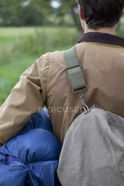 Вид сзади на человека, несущего спальный мешок и рюкзак — стоковое фото