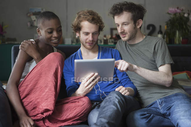 Friends using digital tablet together on sofa at home — Stock Photo