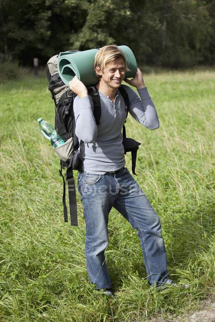 Улыбающийся человек с рюкзаком и катаной коврик в природе — стоковое фото