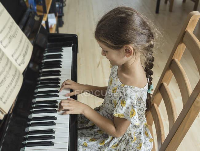 Vista ad alto angolo di ragazza che suona il pianoforte a casa — Foto stock