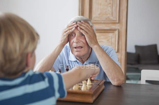 Homem idoso chocado com a cabeça nas mãos olhando para o neto enquanto joga xadrez em casa — Fotografia de Stock