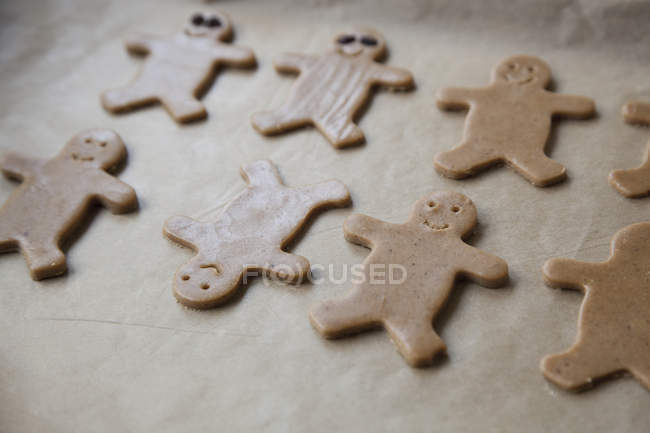 Close up of gingerbread men cookies on baking sheet — Stock Photo