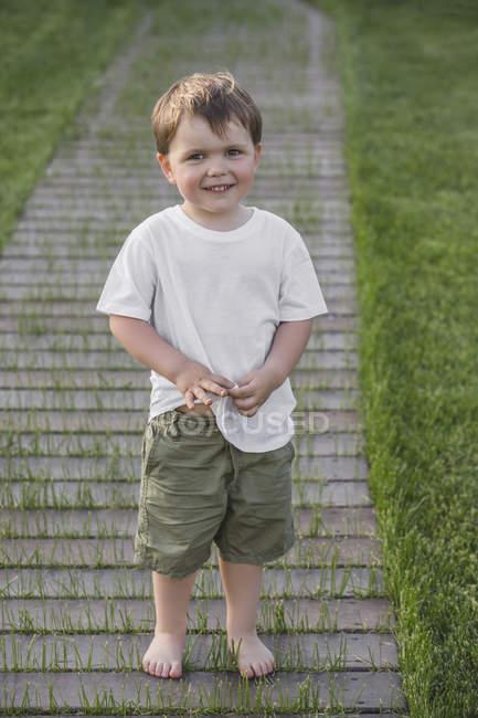 Retrato de menino bonito em pé no caminho do parque — Fotografia de Stock