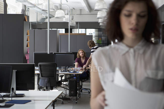 Colleagues discussing in office, Woman with documents in foreground — Foto stock