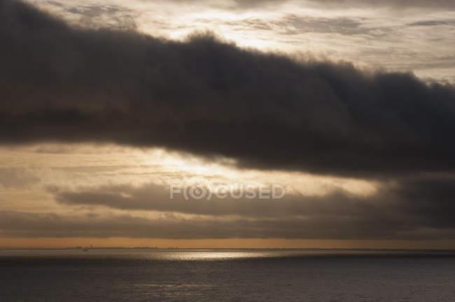 Vue panoramique sur mer contre ciel nuageux pendant le coucher du soleil — Photo de stock