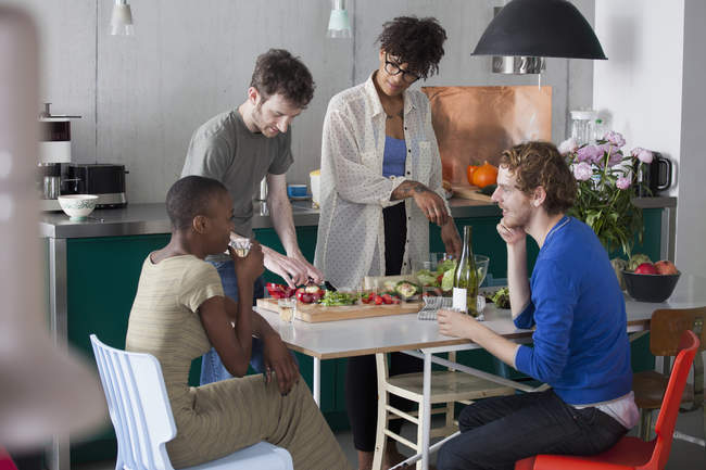 Friends preparing food at table in kitchen — Stock Photo
