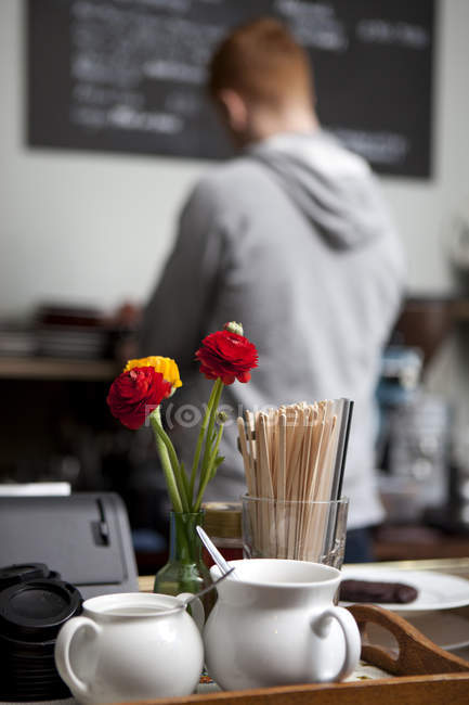 Close up of condiments at  cafe with barista in background — Stock Photo