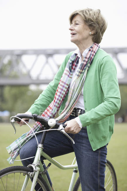 Mature woman cycling bicycle in park — Stock Photo