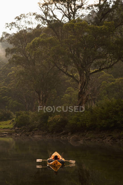 Serene landscape with man relaxing in inflatable raft on lake — Stock Photo