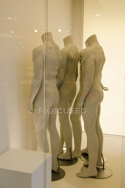 Side view of mannequins by wall seen through glass at store — Stock Photo