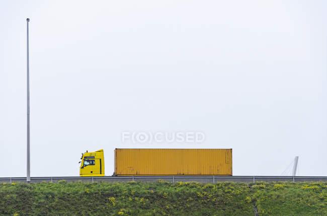 Semi-camion jaune sur pont contre ciel clair — Photo de stock